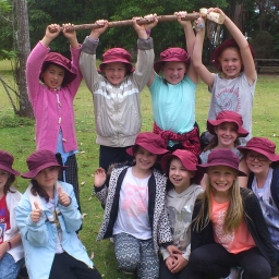 Tathra Public School students holding up a rake they have built by hand.
